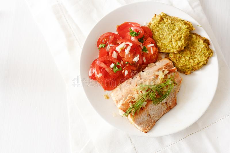 Fried salmon with vegetable pancakes and tomatoes, low carb diet food on white table with copy space, high angle view from above stock photo