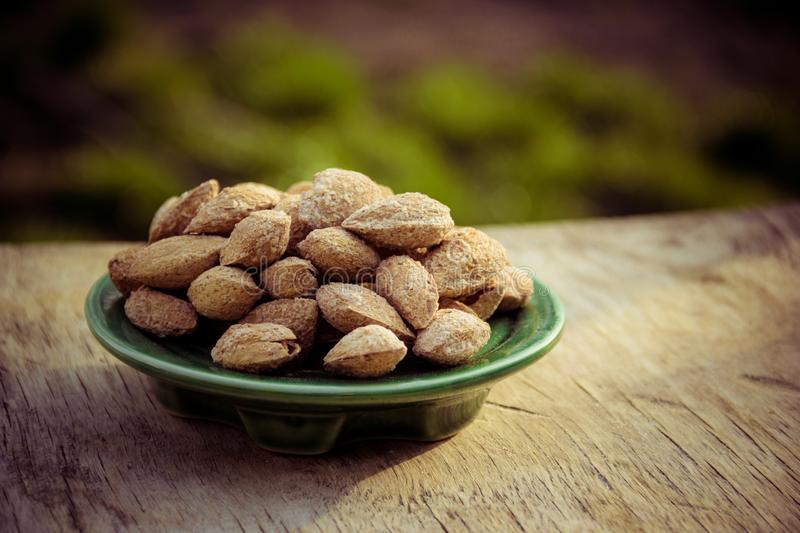 Fried salted almonds in shell. Useful nuts on wooden background. stock photos