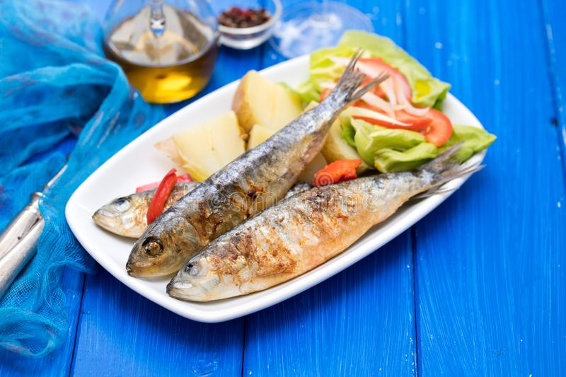 Fried sardines with boiled potato and salad on plate royalty free stock images