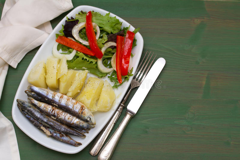 Fried sardines with boiled potato and salad stock photo