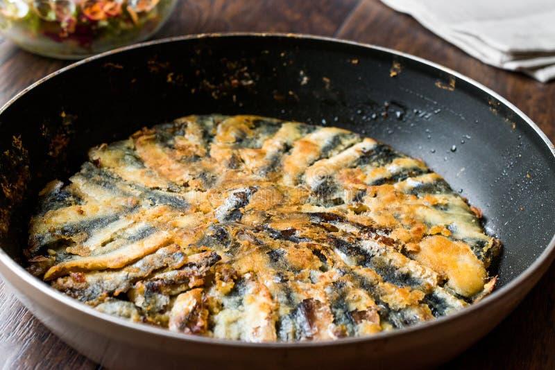 Fried Sardines frais dans la casserole avec de la salade sur la surface en bois photos libres de droits