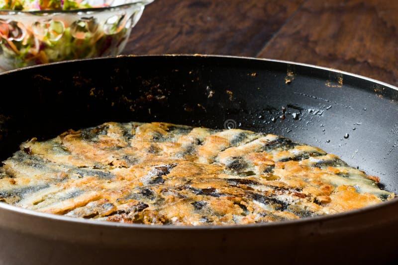 Fried Sardines frais dans la casserole avec de la salade sur la surface en bois image libre de droits
