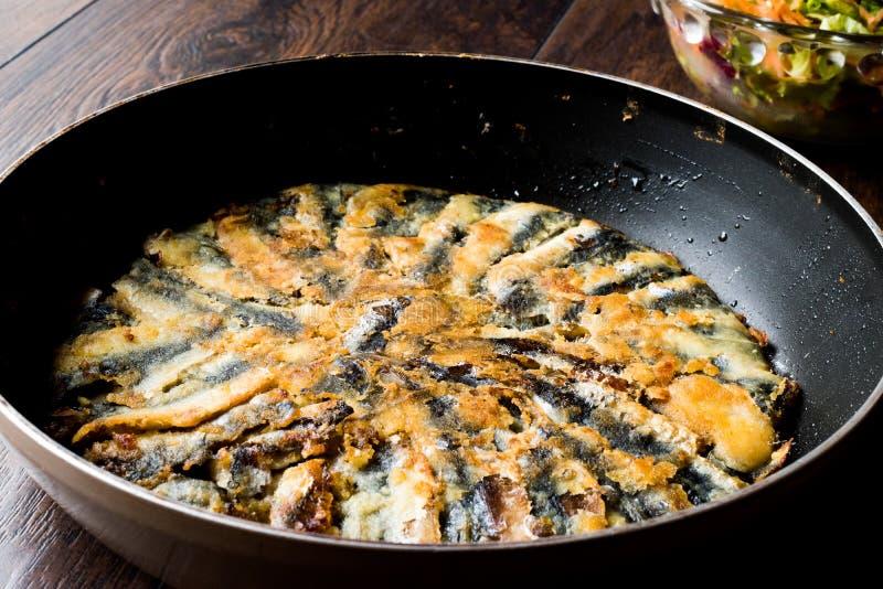 Fried Sardines frais dans la casserole avec de la salade sur la surface en bois photographie stock