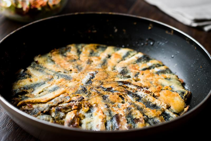 Fried Sardines frais dans la casserole avec de la salade sur la surface en bois photographie stock libre de droits