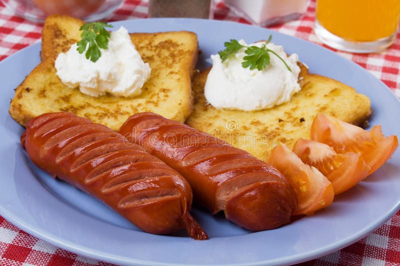 Fried sausage and french toast. Fried sausage served with sour cream and french toast stock photos