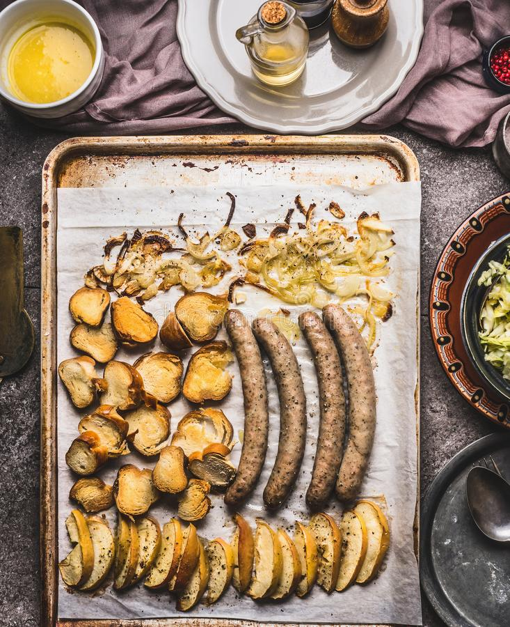 Fried sausages on baking tray with baking apples, onions and lye bun toast with mustard dip. Top view royalty free stock photos