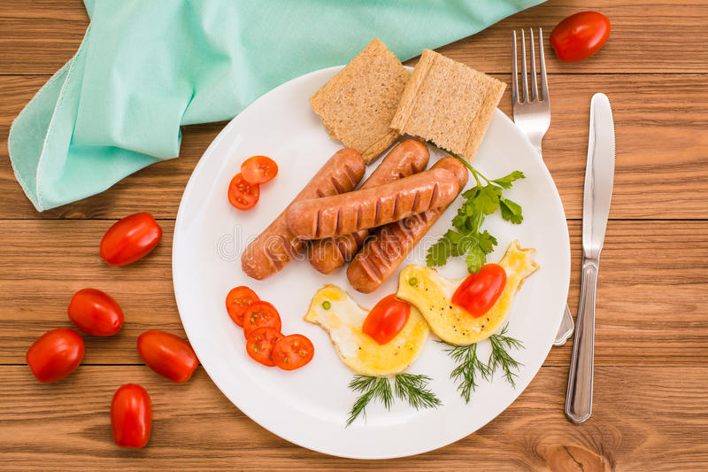 Fried sausages, scrambled eggs, cherry tomatoes and bread. stock photo