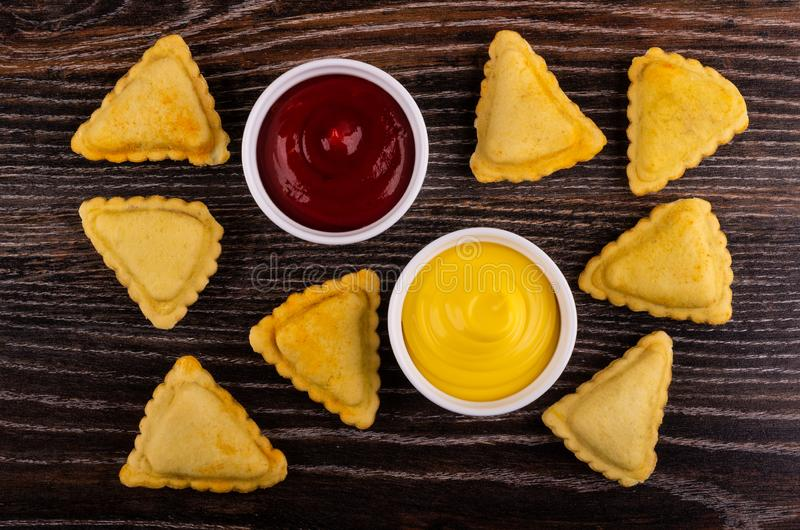 Fried savory pies, bowls with ketchup, mayonnaise on table. Top view. Small fried savory pies, bowls with ketchup and mayonnaise on wooden table. Top view royalty free stock photography