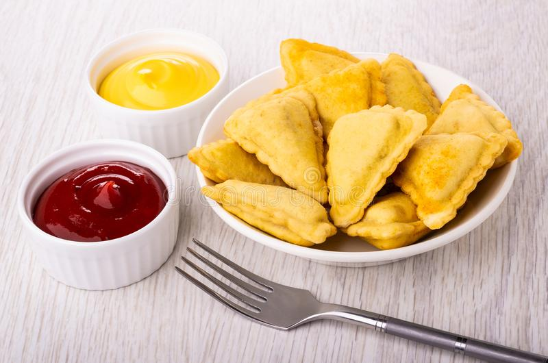 Fried savory pies in plate, bowls with mayonnaise and ketchup, fork on table. Small fried savory pies in white plate, bowls with mayonnaise and ketchup, fork on royalty free stock photos