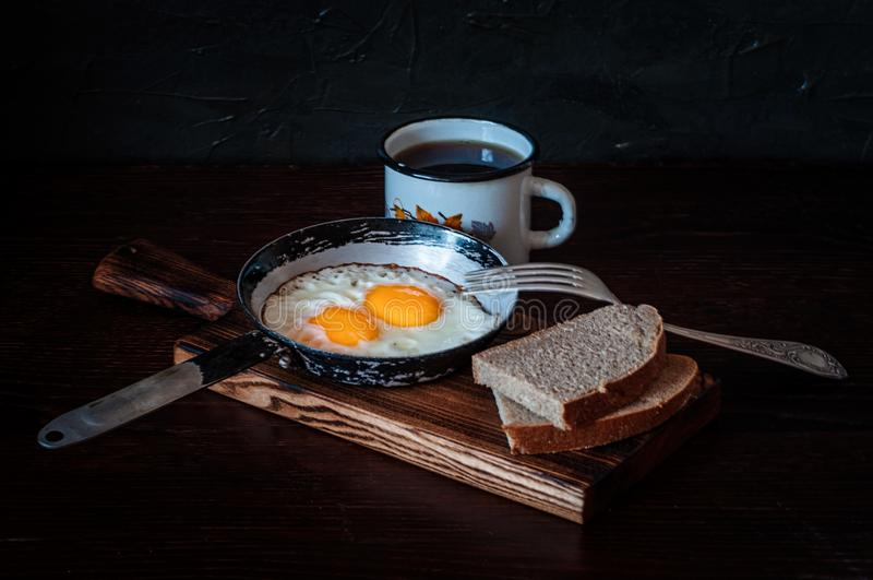 Fried scrambled eggs in a vintage pan, with bread, metal mug with tea stock photo