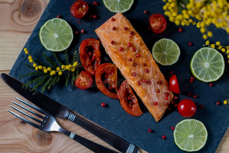 Fried sea fish with pieces of a tomato and a lime. royalty free stock photos