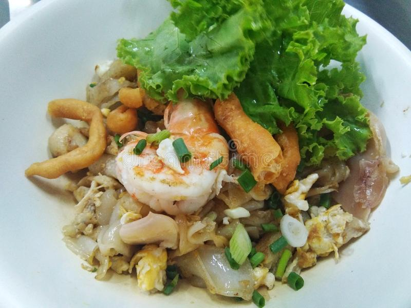 Fried seafood noodles with egg. Food, dinner, thai, asian, lunch, dish, cuisine, seafood, vegetables, delicious, prawns, restaurant, green, style, meal stock photo