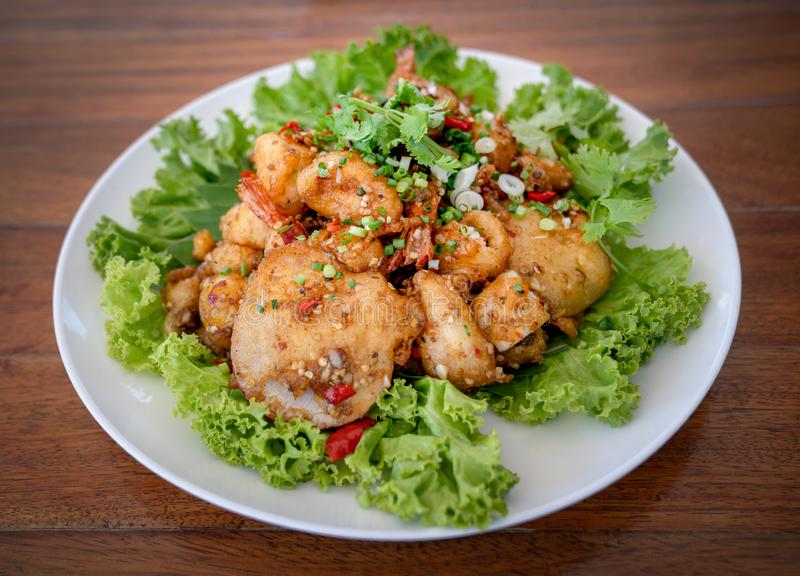 Fried Seafood shrimp prawn fish mussel squid fish on the salad vegetagle in white circle dish on wood table. Fried Seafood shrimp prawn fish mussel squid fish on royalty free stock photos