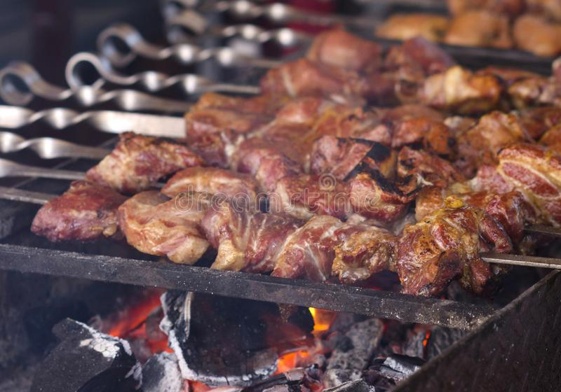 The fried shish kebab cooking on a metal spit. Fried meat is made in a barbecue. On charcoal. Street food stock image
