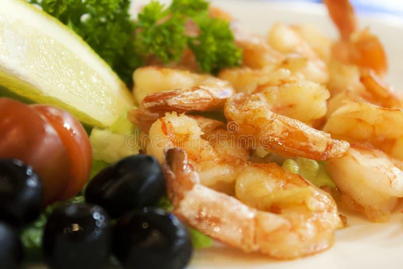 Fried shrimp and lemon, olives, lettuce, tomato and sauce royalty free stock photo