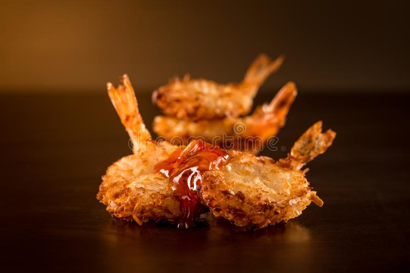 Fried shrimp with sauce in a dark ambient. Four Fried shrimp with sauce in a dark ambient royalty free stock photos