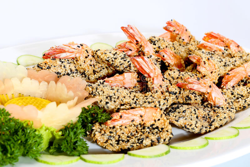 Fried shrimp with seasame and sliced cucumber on white dish royalty free stock photo