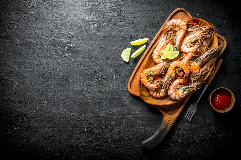 Fried shrimps on a cutting Board with slices of lime and tomato sauce. On black rustic background stock photos