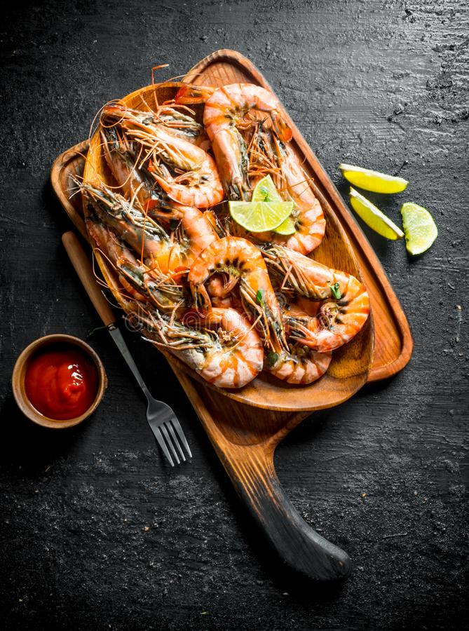 Fried shrimps on a cutting Board with slices of lime and tomato sauce. On black rustic background stock images