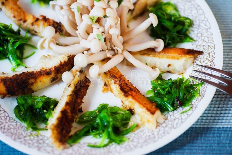 Fried skivade fisken, havsväxt och shimejichampinjonen på plattan, closeup arkivfoton