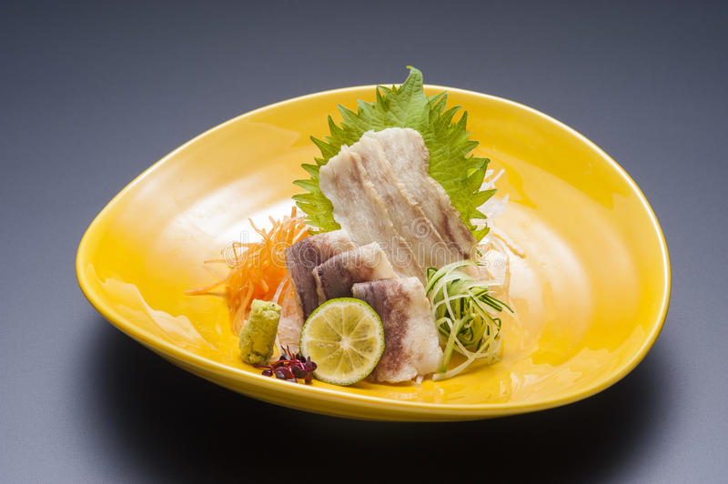 Fried sliced pork with wasabi and sliced lime on platter stock photography