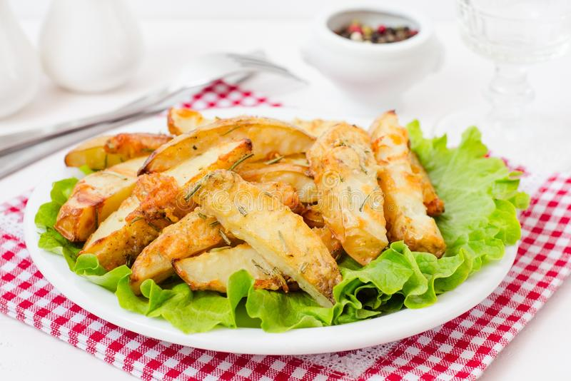 Fried sliced potatoes with lettuce on white plate in restaurant stock image