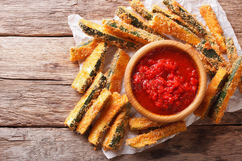 Fried slices of zucchini with parmesan cheese and breading and t. Fried slices of zucchini with parmesan cheese and breading and spicy tomato sauce closeup on a stock photos