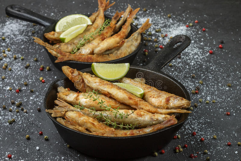 Fried smelt in a frying pan on the table with spices, lime and thyme stock photography