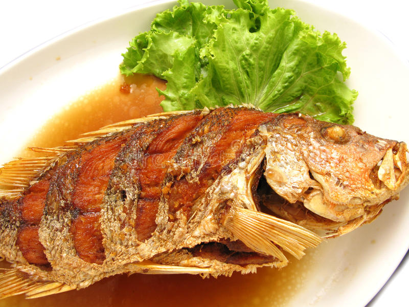 Fried snapper with fish sauce on the dish. At restaurant stock photography