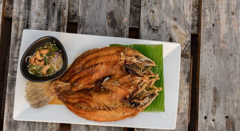 Fried Snapper profundo remató con la salsa de pescados dulce en la tabla de madera fotografía de archivo