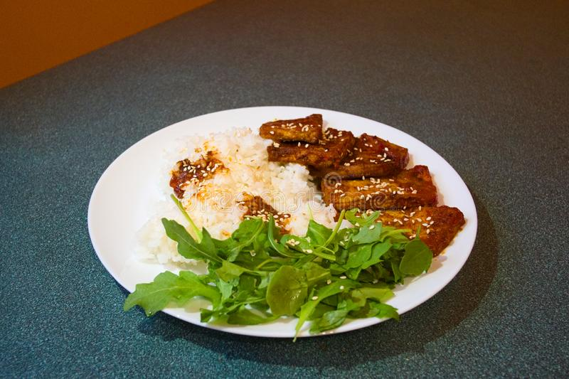 Fried soy meat stewed in tomato sauce and spices with boiled rice. Served on white plate with fresh green arugula leaves. Close up. Selective focus royalty free stock image