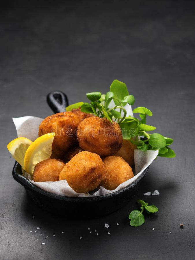 Fried Spanish bacalao croquettes in iron pan made with breaded salted codfish and served as traditional tapas or snacks. Dark royalty free stock photography
