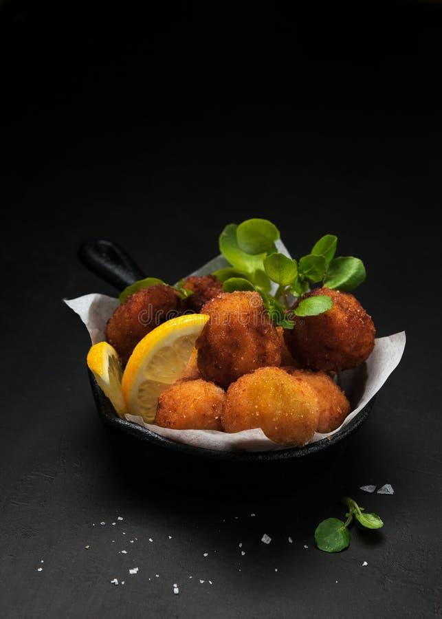 Fried Spanish-de bacalaocroquetten in ijzerpan maakten met gepaneerde gezouten kabeljauw en gediend als traditionele tapas of sna stock fotografie