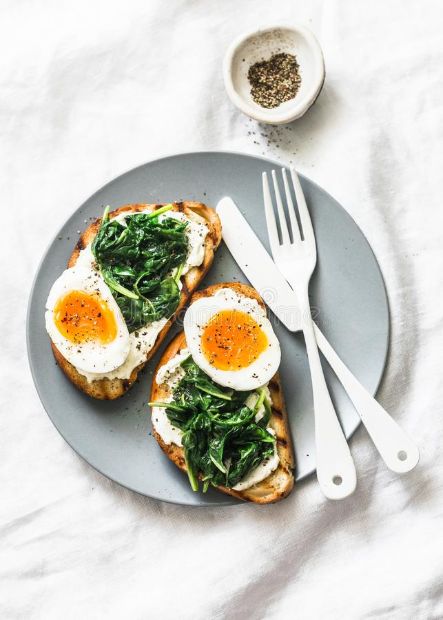 Fried spinach, labne and boiled eggs sandwiches - delicious healthy breakfast or snack on a light background royalty free stock photography