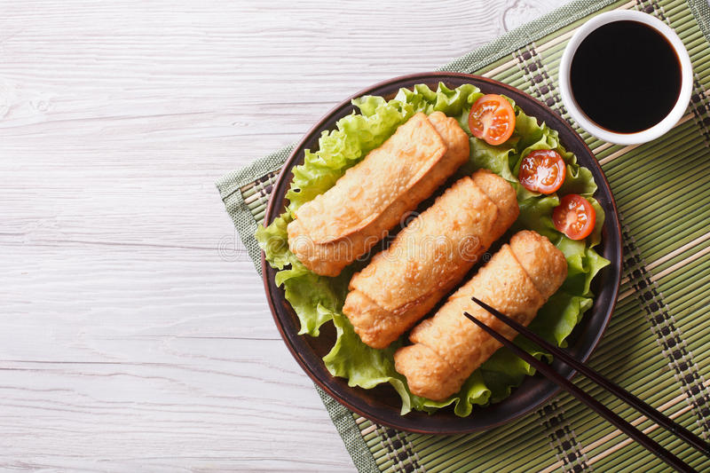 Fried spring rolls on a plate with salad, horizontal top view. Fried spring rolls on a plate with salad, horizontal view from above stock photos
