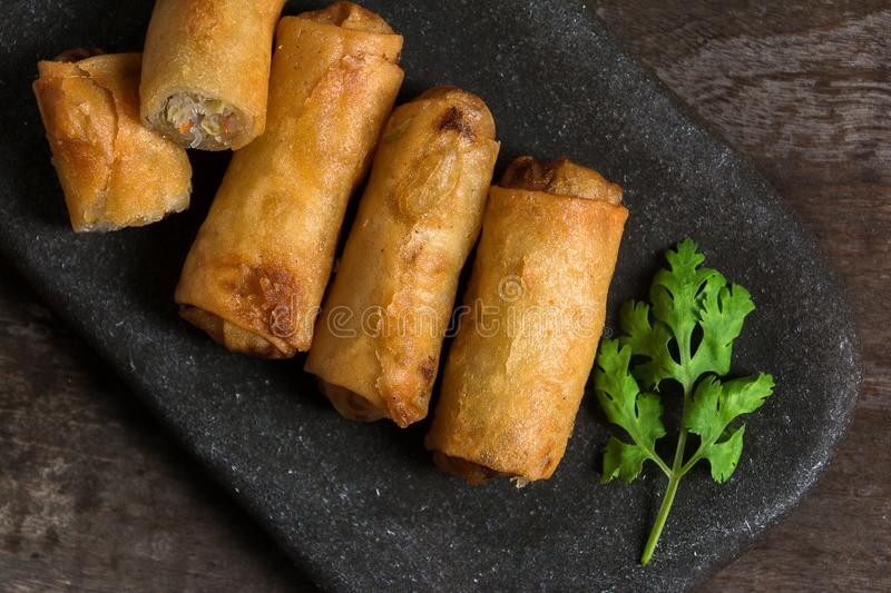 Fried Spring Rolls Stacked on black slate plate on wooden.top vi. Ew stock image