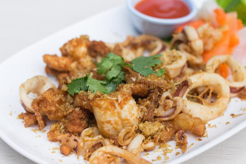 Fried squid with garlic in white dish on the table royalty free stock photography