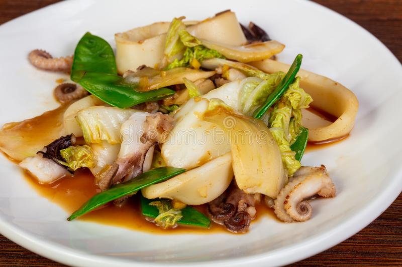 Fried squid with green peas royalty free stock images