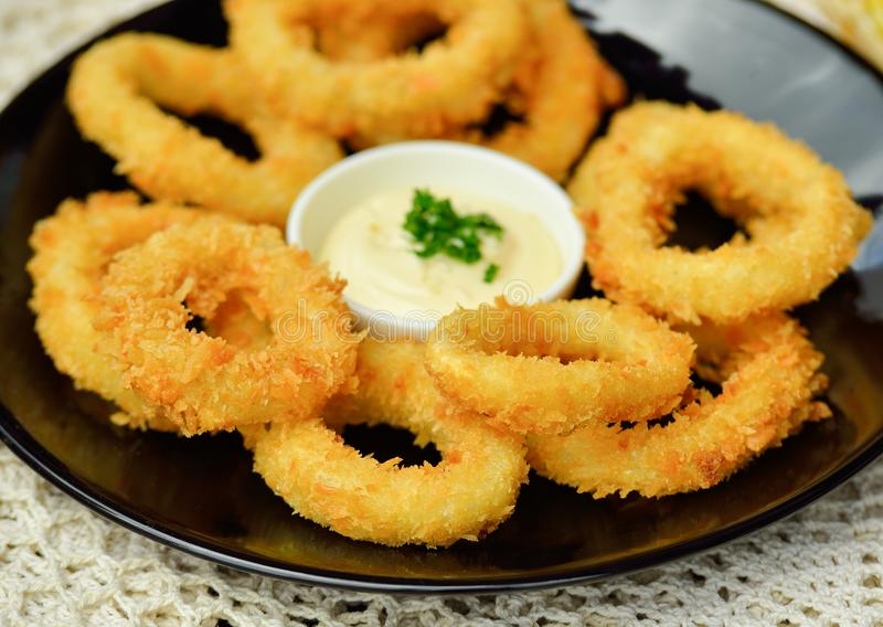 Fried squid rings breaded on wooden background stock images