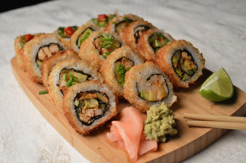 Delicious fried sushi served in a wooden board royalty free stock image