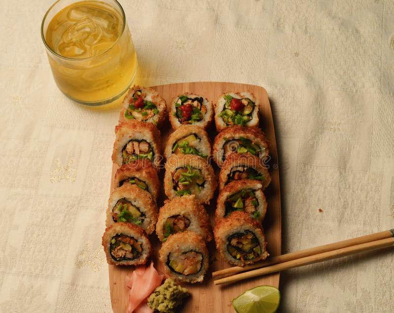 Delicious fried sushi served in a wooden board stock image