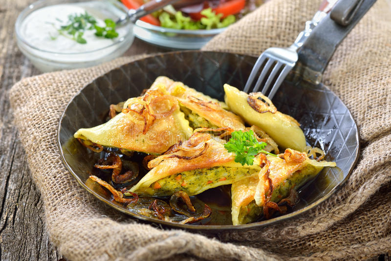 Fried Swabian ravioli. (so called 'Maultaschen') with vegetable filling served with side salad and creamy herb cheese royalty free stock photography