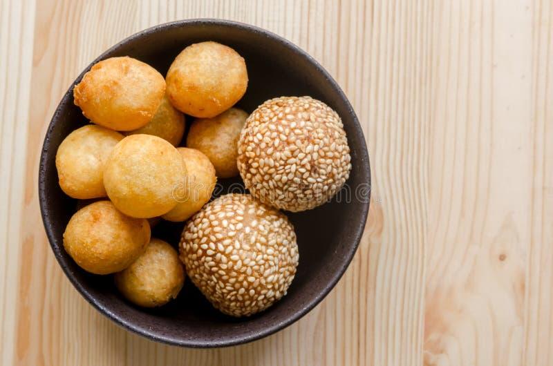 Fried Sweet Potato Balls profond dans la cuvette noire sur la table en bois photographie stock