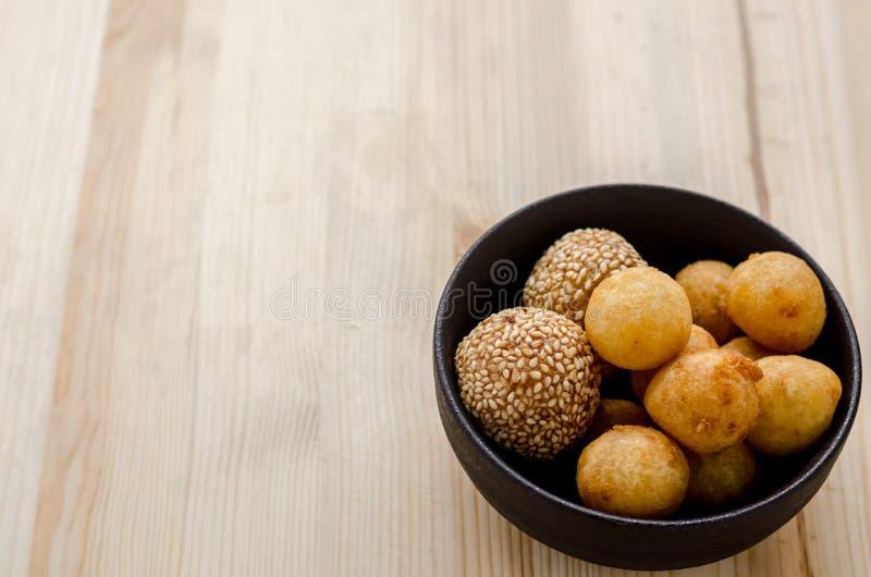 Fried Sweet Potato Balls profond dans la cuvette noire sur la table en bois image libre de droits