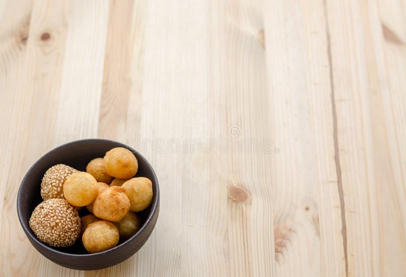Fried Sweet Potato Balls profond dans la cuvette noire sur la table en bois photos libres de droits