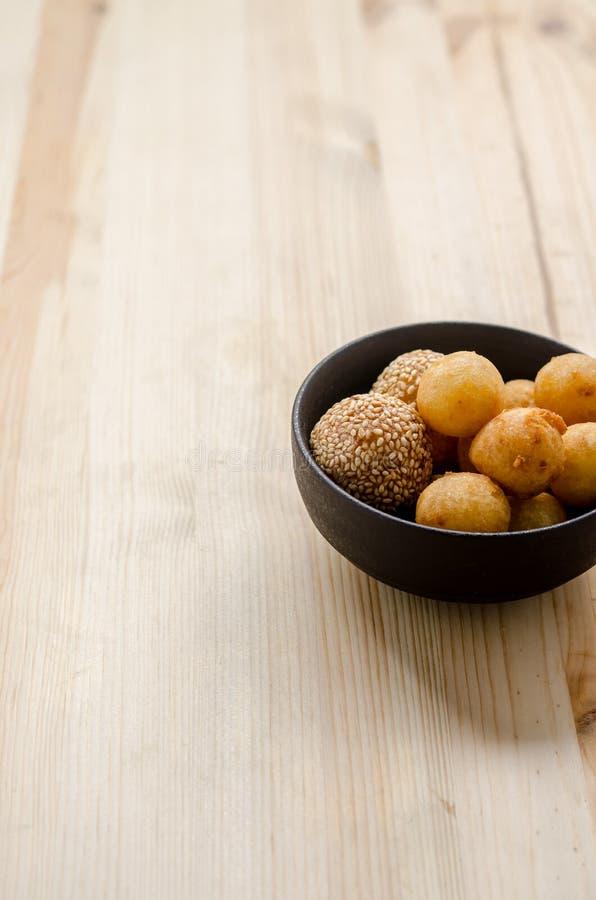 Fried Sweet Potato Balls profond dans la cuvette noire sur la table en bois photographie stock libre de droits