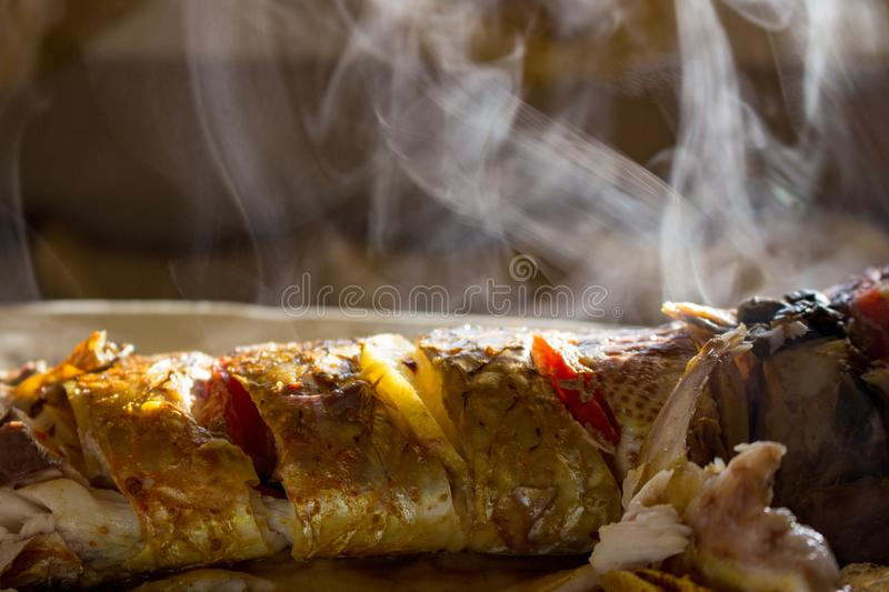 Fried tasty fish with lemon and tomato with smoke. Grilled fish with crisry crust and smoke retro. Delicious fish in sunligt. stock photos