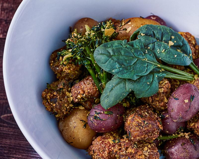 Fried Tempeh Balls in a White Bowl. Fried Tempeh Balls in a stir fry with other vegetables in a white bowl stock image