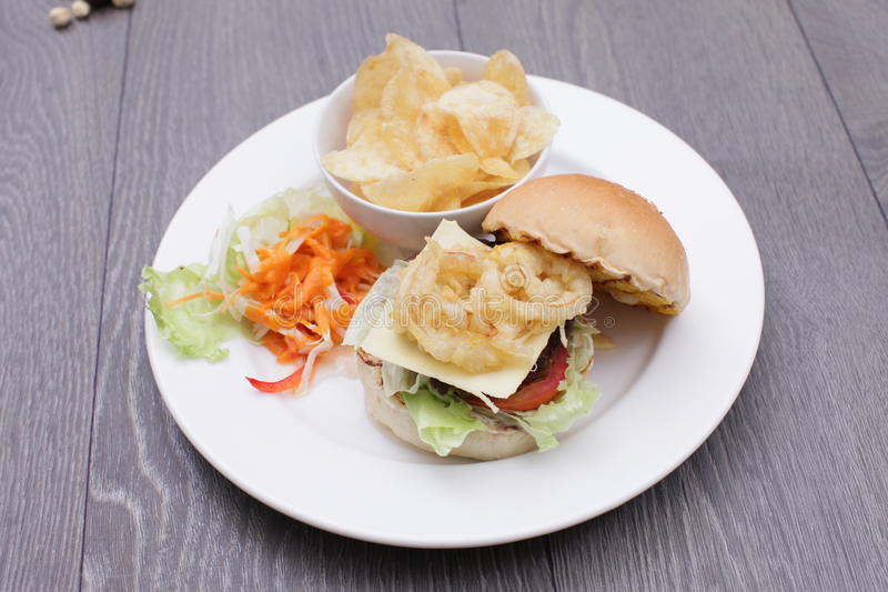 Fried tempura hamburger with fried potatoes and salad on white p stock photography