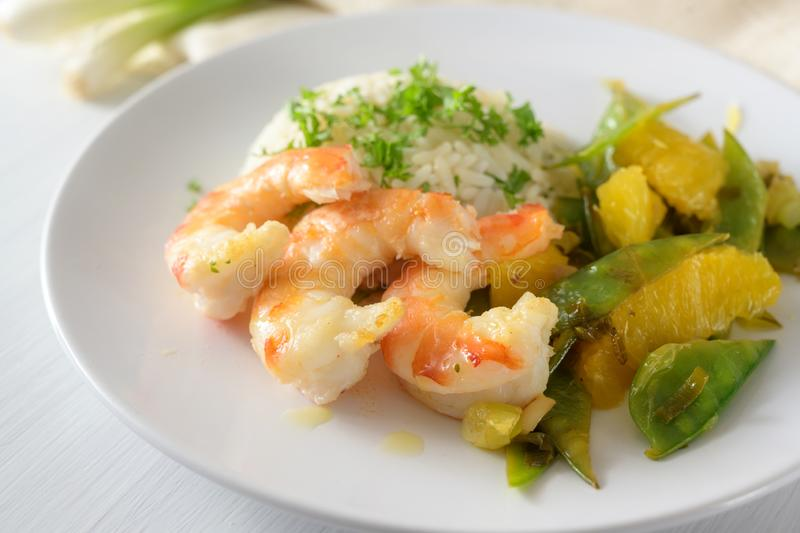 Fried tiger prawn shrimp dish with sugar peas, onion and oranges served with rice and parsley garnish on a white plate, selected. Focus, narrow depth of field royalty free stock image